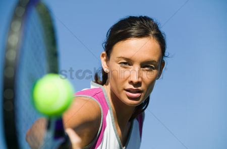 Physical : Female tennis player hitting ball close up of racket focus on player