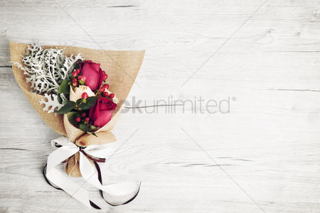 Conceptual : Flatlay of wooden background with bouquet of roses
