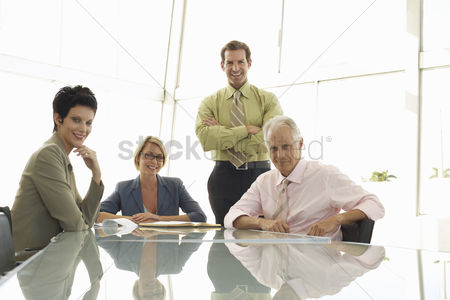 Posed : Four businesspeople in meeting