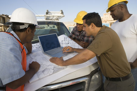 Car : Four construction workers standing in front of car on construction site