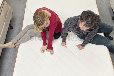 Shopping : Friends sitting on mattress in furniture store