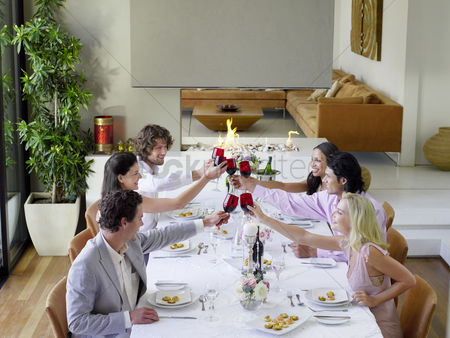 Arm raised : Friends toasting across table at a formal dinner party side view