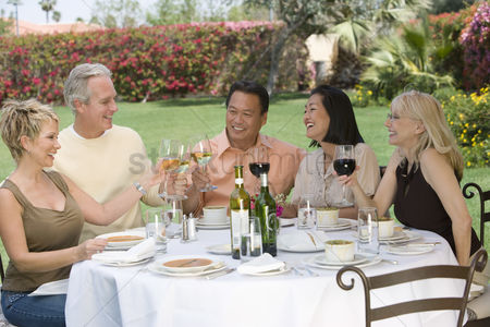 Wine bottle : Friends toasting at outdoor table