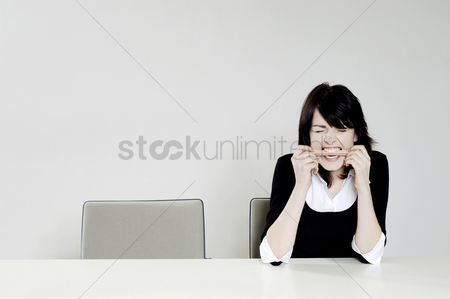 Executive : Frustrated businesswoman biting a pencil