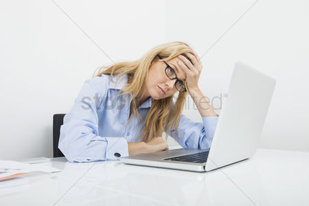 Young woman : Frustrated businesswoman looking at laptop in office