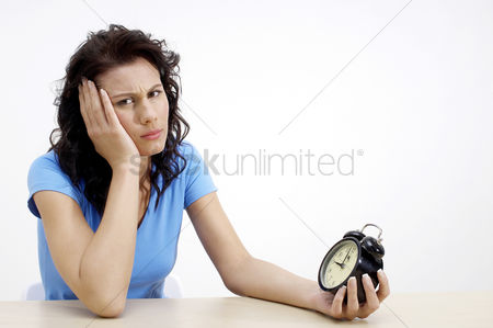 Thought : Frustrated woman holding an alarm clock