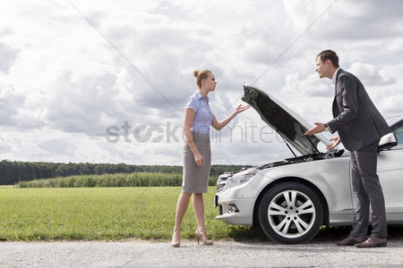 Land : Full length of business couple arguing by broken car at countryside