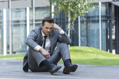 Worry : Full length of depressed businessman sitting on path outside office