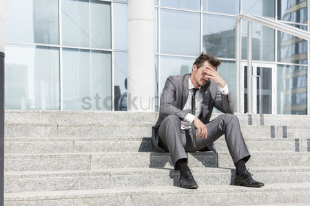 Worry : Full length of depressed businessman sitting on steps outside office