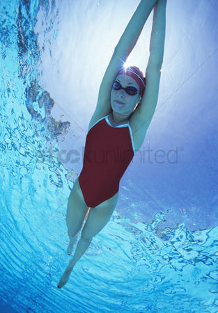 Swimmer : Full length of female swimmer in united states with arms raised swimsuit swimming in pool