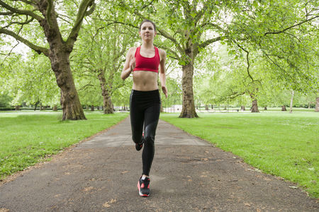 Grass : Full length of fit young woman jogging in park