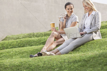 Steps : Full length of happy businesswomen looking at laptop while sitting on grass steps against wall