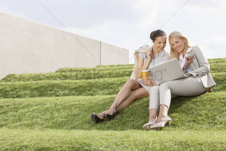 Steps : Full length of happy businesswomen looking at laptop while sitting on grass steps