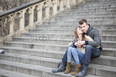 Kissing : Full length of loving woman kissing man while sitting on steps outdoors