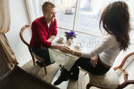 Girlfriend : Full length of romantic couple holding hands in cafe