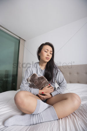 Pain : Full length of sad young woman with hot water bottle on stomach in bedroom