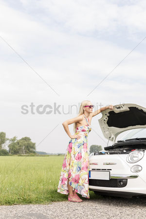On the road : Full-length of tensed woman standing by broken down car on country road
