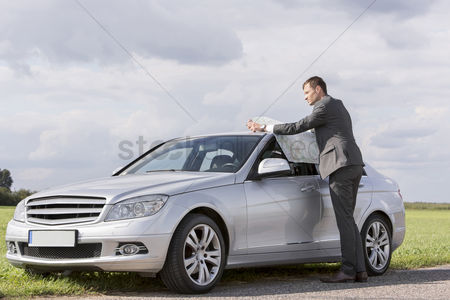 Land : Full length of young businessman reading map by car at countryside