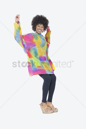Traditional clothing : Full length portrait of happy african american woman in dashiki dancing over gray background