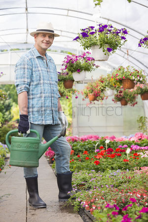 Greenhouse : Full-length portrait of smiling man carrying watering can in greenhouse