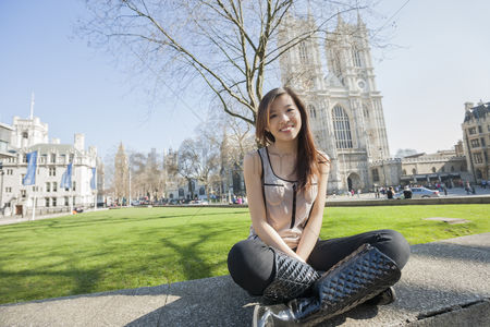England : Full length portrait of young woman sitting against westminster abbey in london  england  uk