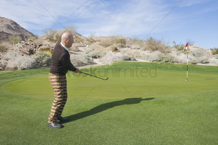 Flag : Full length side view of senior male golfer swinging his club at golf course