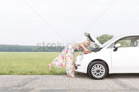 On the road : Full-length side view of woman examining broken down car on country road