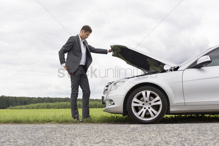 Land : Full length side view of young businessman examining broken down car engine at countryside