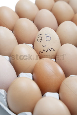Egg tray : Funny face drawn on an egg surrounded by plain brown eggs in carton