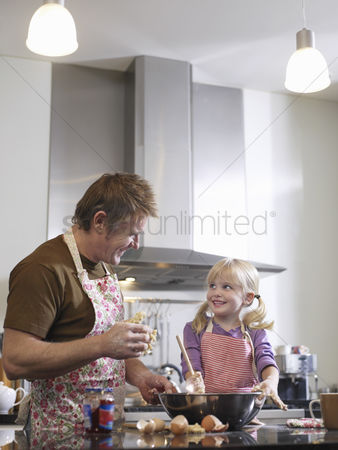 Apron : Girl  3-4  and father baking in kitchen