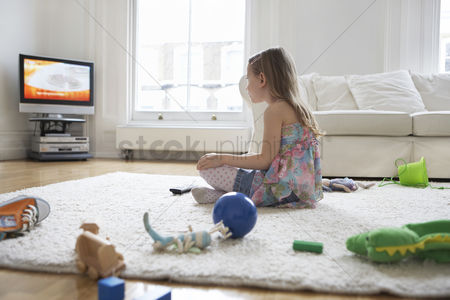 Toy : Girl  5-6  sitting on floor surrounded with toys watching television
