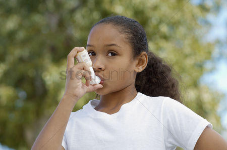 Medication : Girl  7-9  using inhaler outdoors