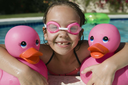 Posed : Girl at pool side holding pink rubber ducks