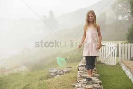Posed : Girl balancing with butterfly net on wall