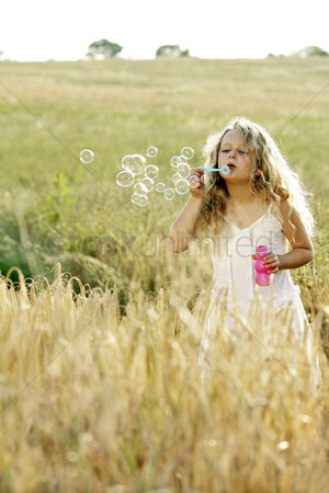 Blowing : Girl blowing bubbles in the field
