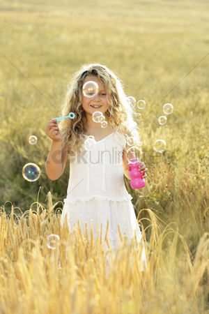Curly hair : Girl blowing bubbles in the field