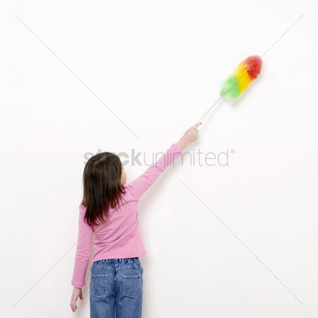 Kid : Girl dusting the wall with a feather duster