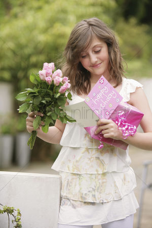 Birthday present : Girl holding a bouquet of flowers and present while reading birthday card