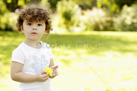 Enjoying : Girl holding a yellow flower