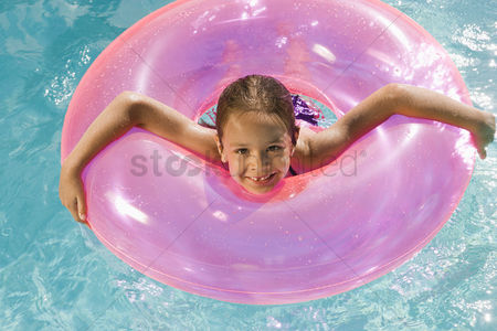 Pink : Girl inside pink float tube in pool