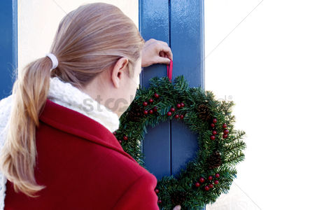 Bliss : Girl putting up a wreath on the door