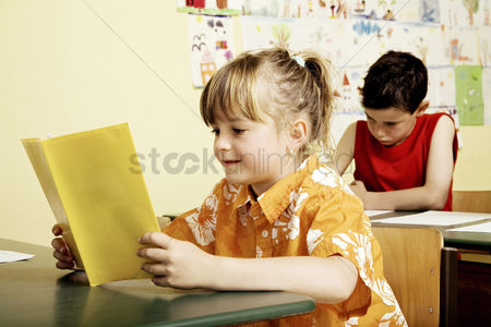 School children : Girl reading in the classroom