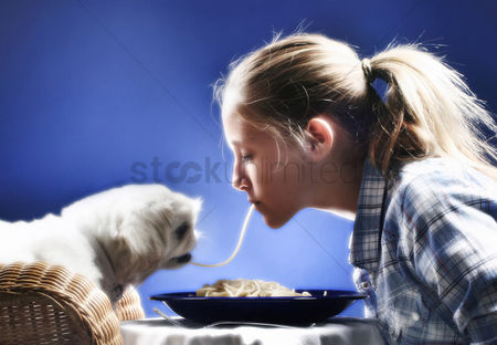 Appetite : Girl sharing spaghetti with her dog