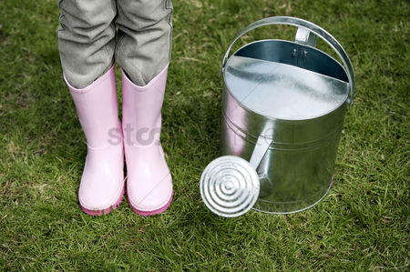 Outdoor : Girl standing beside watering can