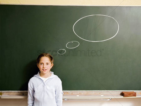 Cartoon : Girl standing in front of a blackboard with thought bubble