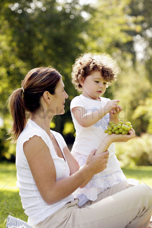 Three quarter length : Girl taking a green grape from her mother