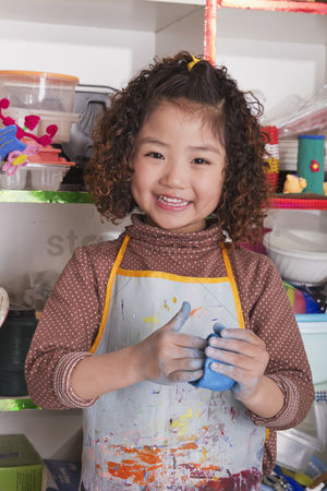 Proud : Girl wearing apron and playing with clay