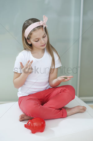 Pocket : Girl with red piggy bank counting coins on bed