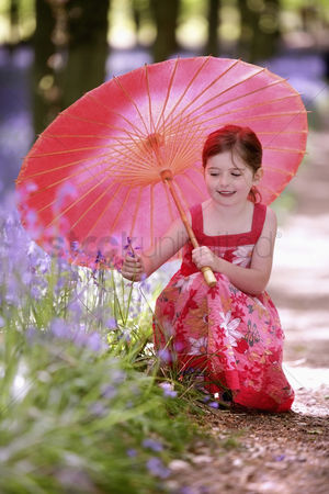 Spring : Girl with umbrella looking at flower