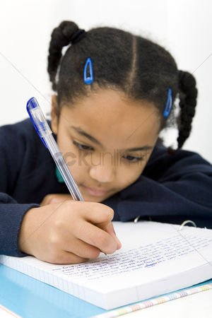 School children : Girl writing on paper